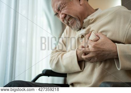 Asian Senior Disabled Male With Chest Pain Suffer From Heart Attack. Elderly Older Male On Wheelchai