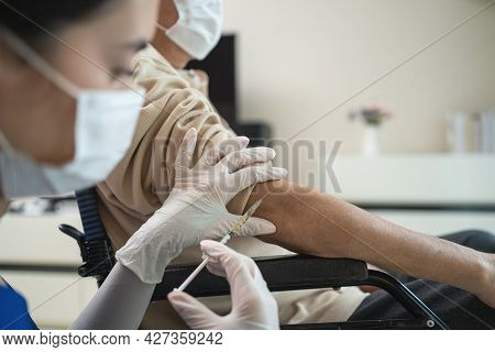 Caucasian Doctor Give Treatment To Senior Elderly Man Disabled Patient. Beautiful Therapist Girl Or