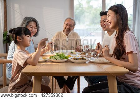 Asian Big Happy Family Spend Time Have Lunch On Dinner Table Together. Little Kid Daughter Enjoy Eat