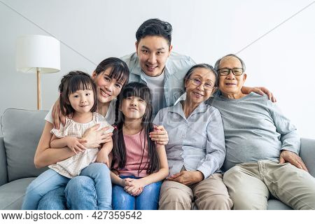 Portrait Of Asian Happy Family Sit On Sofa And Smile, Look At Camera. Young Couple Parents Spend Tim