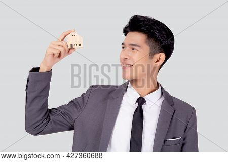 Young Asian Business Man Holding The Home Symbol Of Saving For Future, Insurance Agent And Credit, O