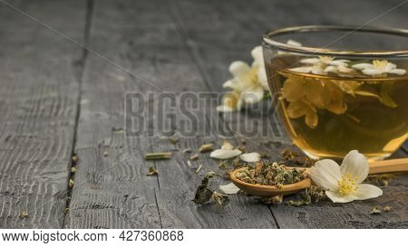 A Cup Of Fresh Tea With Jasmine Flowers On A Black Wooden Table. An Invigorating Drink That Is Good