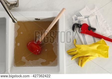 Kitchen Counter With Clogged Sink, Plunger And Plumber's Accessories, Flat Lay