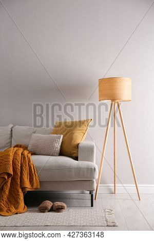 Stylish Living Room Interior With Comfortable Sofa And Tripod Floor Lamp. Space For Text