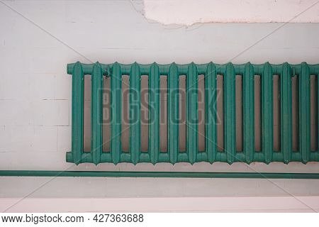 Old-fashioned Green Heating Radiator On A Grey Tile Wall. Indoor Heating System.