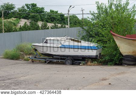 An Old Dilapidated Fishing Boat On A Trailer In Front Of A Gray Fence. Car Trailer With A Flat Tire