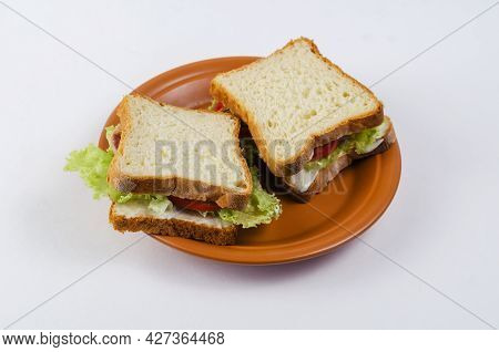 Tuna Sandwiches In A Brown Plate On A White Background. Two Brown Sandwiches With Fish, Red Tomatoes