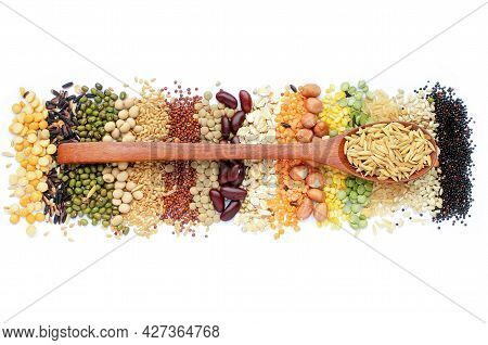 Dry Organic Rice Seed In Wooden Spoon On Variety Kinds Of Natural Cereal And Grain Seed Stripe On Wh