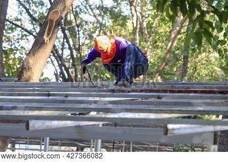 Welding The Roof Truss.welders Working At Dangerous Heights. Welding Of Steel Is Very Technically De