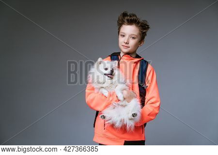 Cheerful Cute Schoolboy Of Caucasian Ethnicity In Bright Clothes With A Backpack And A Dog In His Ha