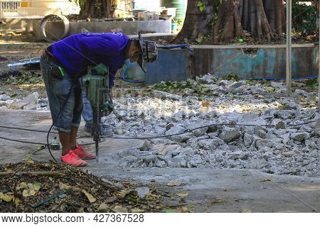 A Worker Is Using A Drilling Rig Used To Drill The Cement Floor.