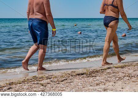 The Lower Body Of Two Elderly People Walking Along The Coastline Of The Sea. Old Man In Swimming Tru