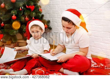 Children With Letter To Santa At Home During Christmas. Two Cute Little Brothers Writing A Letter To