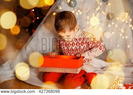 Surprised Cute Child Opening A Christmas Present. Little Kid Having Fun Near Decorated Tree Indoors.