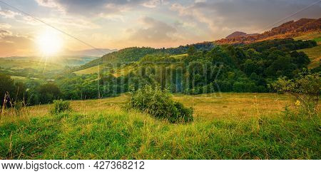 Mountainous Rural Landscape At Sunset. Beautiful Scenery With Forests, Hills And Meadows In Evening