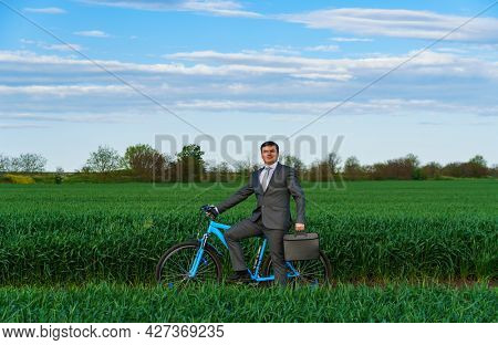 Businessman rides a bicycle in a green grass field - business concept for freedom, vacation or freelance. Beautiful spring nature.