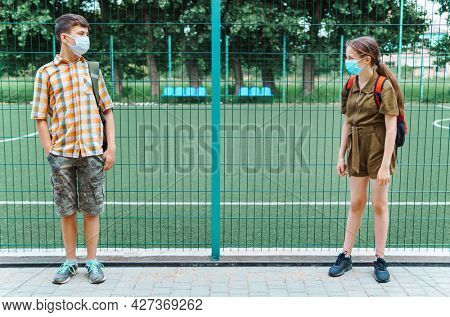 two teenagers boy and girl on the way to the school, they use protective face masks, stand by the playground and show social distance to protect against coronavirus infection