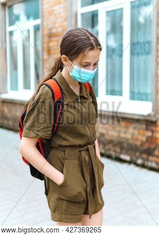 teen schoolgirl on the way to the school, they use protective face masks to protect against virus, coronavirus infection, education and back to school concept
