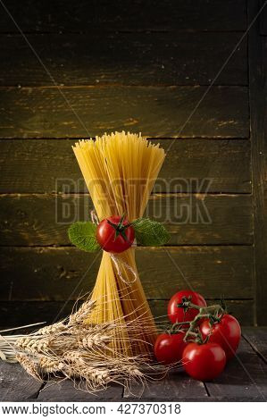 Spaghetti And Tomatoes. Spaghetti And Spikelets Of Wheat. Spaghetti And Rustic Style. Vertical Frame
