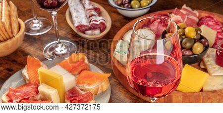 Gourmet Wine Appetizers Panorama With A Glass Of Rose Wine, A Cheese And Charcuterie Board, And Salm