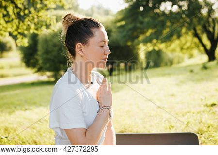 Profile Portrait Young Woman Meditates In Yoga Asana Pose In Morning Park, Outdoors. Happy Smiling Y