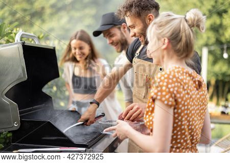 Happy Young Friends Hanging Out Together, Grilling Vegetables And Meat On A Modern Grill At Picnic.