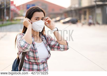 Asian Woman Wearing N95 Face Mask To Protect Pollution Pm2.5 And Virus. Covid-19 Coronavirus And Air