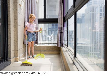 Little Caucasian Blonde Girl With Blonde Hair Seven Years Old Cleaning Floor In Living Room. Modern