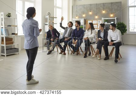 Young Man In The Audience Raises His Hand To Ask The Business Psychologist A Question