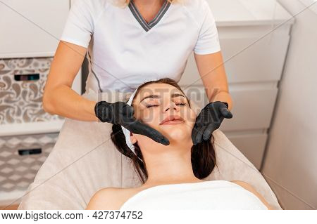 Professional Cosmetologist Gives A Facial Massage To The Client In Salon. Close Up. Top View. Concep