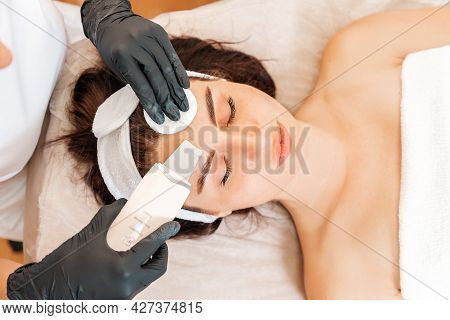 Cleaning Procedure At The Beauty Salon. Cosmetologist Cleans The Client's Forehead Using A Ultrasoni