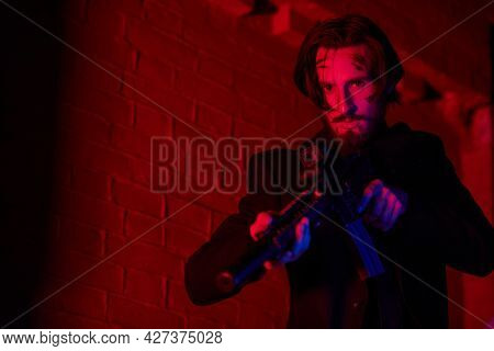 Courageous action hero with automatic guns in an industrial zone  in red and blue lighting at night. Handsome wounded man.