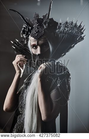 A portrait of fabulous old woman with long gray hair, in a rich headdress and a rich black dress on a gray background. Black Queen, Witch. Halloween.