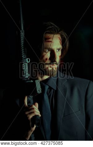 The criminal world in the big city. Courageous man with automatic gun on black background.. Special agent.