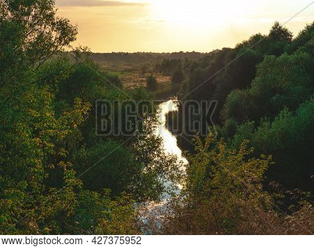 The View On The Solitude River, Trees And Field In Some Rural Area In The Beautiful Sunset. The Summ
