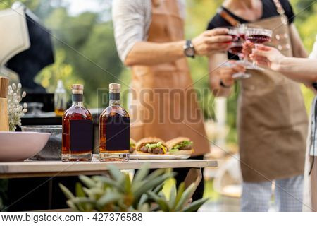 Bottles With Liqueur Or Berry Tinctures On A Table With Burgers, People Cheering On A Background, Cl
