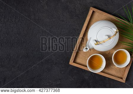 Wooden Tray With Teapot And Tea Cups With Tea Drink Top View On Black Background. Asian Tea Ceremony