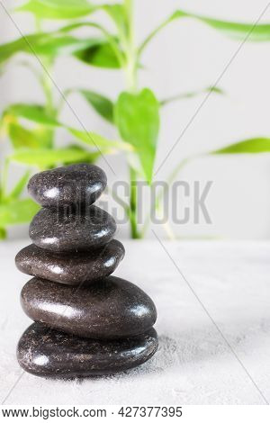 Black Zen Stones In A Stack On White Background With Bamboo.