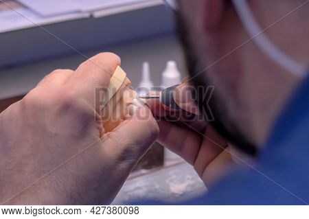 Professional Dental Technician Or Dentist Holding Motor Handpiece Tool And Working With Dental Prost