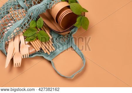 Kraft Paper Food Cups And Containers With Wooden Cutlery In Cotton Net Bag On Kraft Paper Background