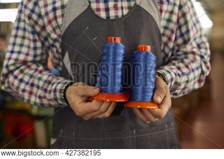 Close Up Of Blue Thread Bobbins In Hands Of Dressmaker, Shoemaker Or Factory Worker