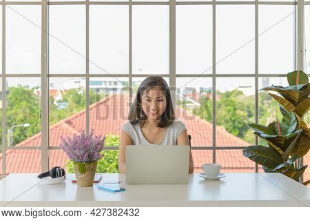 Smiling Young Asian Woman Wear Casual Clothing Working With Computer Laptop In Living Room At Home.
