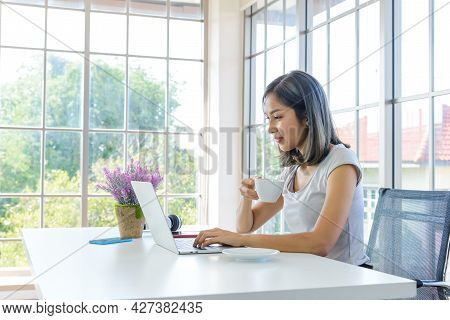 Smiling Young Asian Woman Wear Casual Clothing Working With Computer Laptop And Holding Coffee Mug I