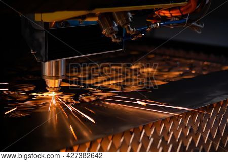 Automatic Cnc Laser Cutting Machine Working With Sheet Metal With Sparks At Factory, Plant. Dark Bac