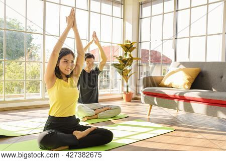 Young Asia Couple Practicing Yoga Lesson, Breathing And Meditating Together In Living Room At Home.