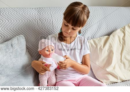 Indoor Shot Of Little Girl Sitting On The Sofa In The Room At Home Playing With Baby Doll, Like Mom,