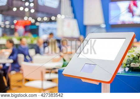 Electronic Multimedia Tablet Kiosk With Blank White Display Against Blurred Business Meeting, Confer