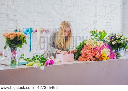 Portrait Of Professional Woman Floral Artist, Florist Making Gift Box With Flowers On Table At Works