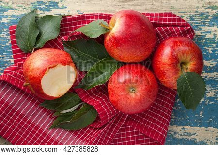 Red Gala Apples Composition With Fresh Green Leaves On Red And White Checkered Napkin. View From Abo