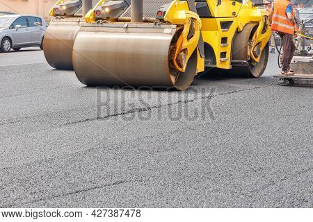 The Metal Cylinders Of The Yellow Road Vibrating Roller Compact The Fresh Asphalt Powerfully On The